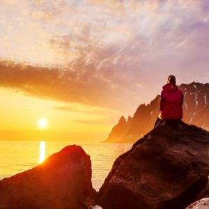 A person watching the midnight sun at Senja in Northern Norway. Photo courtesy of Tobias Bjørkli